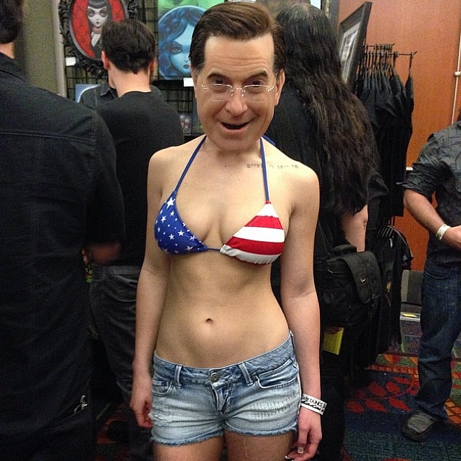 Woman dressed as Stephen Colbert, but looks like a bobble head.